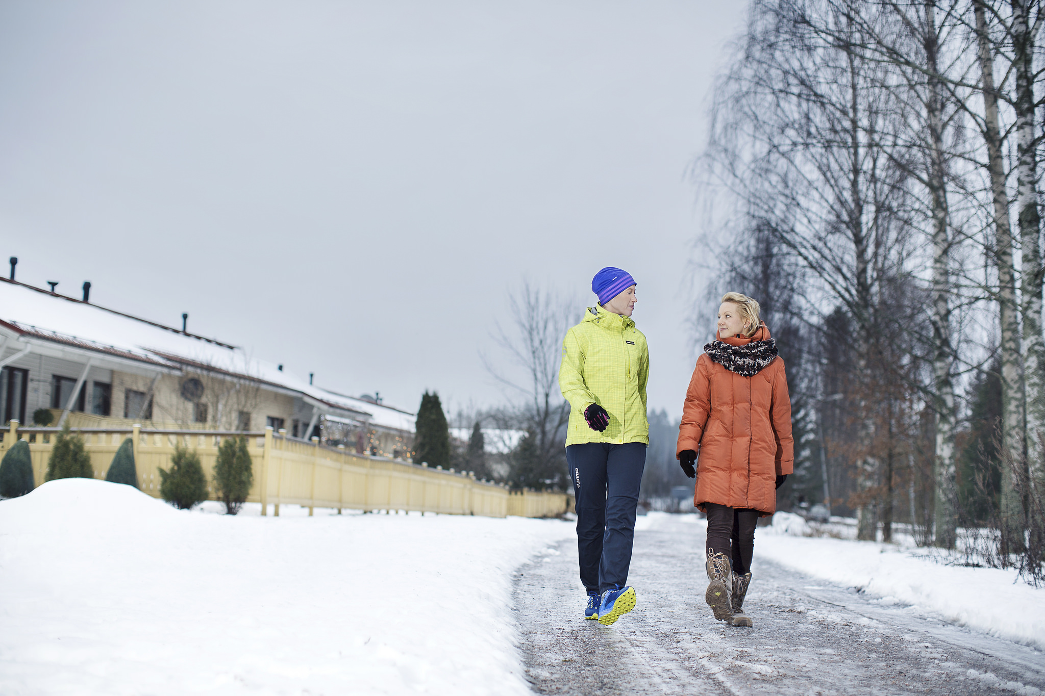 Two people are walking in a slippery road during winter