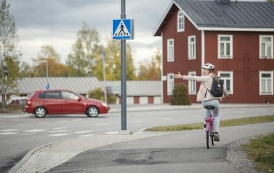Tyttö näyttää suuntamerkkiä autolle