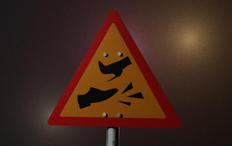 Kuvassa varoituskolmioliikennemerkki, jossa kaksi kenkää liukastumassa.