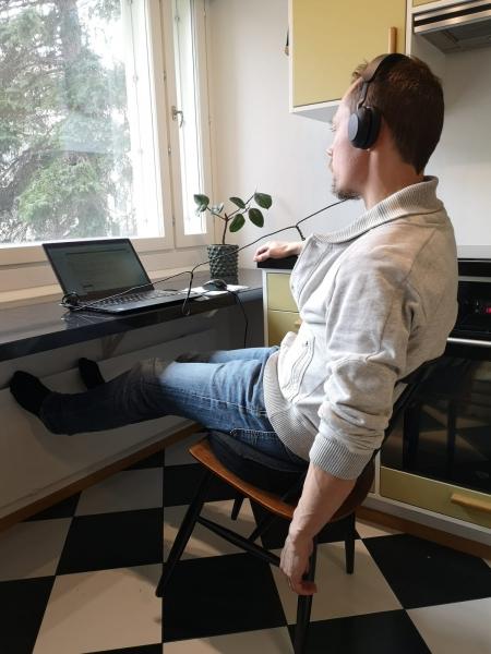 Henkilö keikkuu tuolilla kannettavan tietokoneen edessä.
