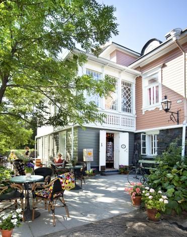Lelumuseo- ja kahvilarakennus kuvattuna ulkopuolelta kesällä. Kuvassa näkyy kahvilan uloterassi ja asiakkaita.