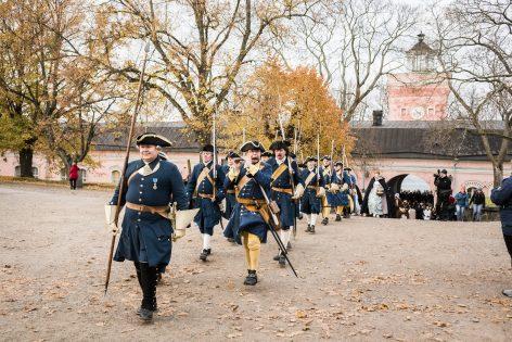 Vanha Warusväki kävelemässä univormuissa läpi Rantakasarmin holvikaaren.