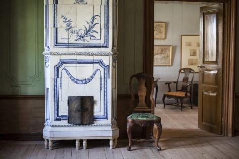 Sisäkuva Ehrensvärd-museosta, jossa näkyy vanha koristeellinen takka ja pari tuolia.