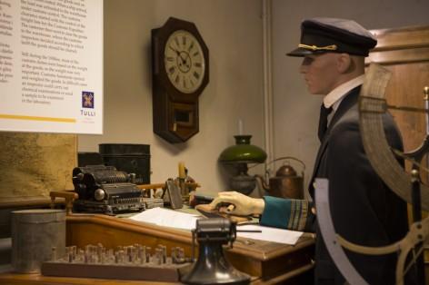 Tullimuseon sisätilan nukke, joka esittää tullin työntekijää työpöytänsä ääressä.