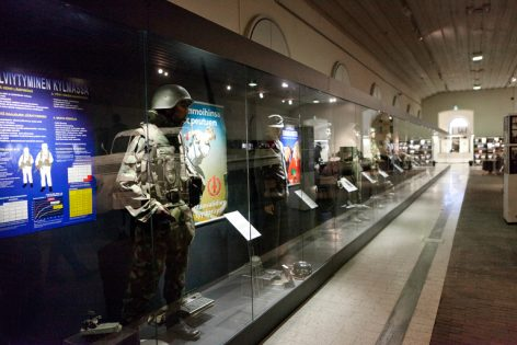 Sotamuseon maneesin näyttelytila, jossa näkyy vitriineissä mallinukkeja erilaisissa univormuissa.