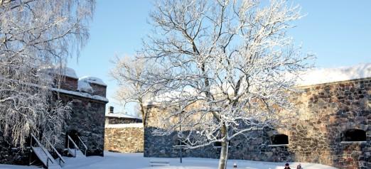 Talvinen Suomenlinnan, kaksi ihmistä kävelee muurien välissä.