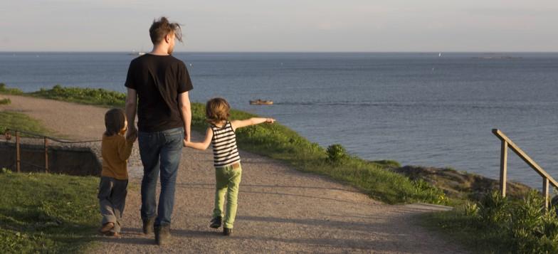 Isä ja kaksi poikaa kävelemässä käsi kädessä Kustaanmiekalla.