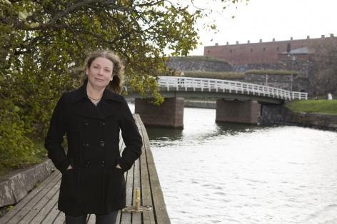 Iina Johansson seisoo laiturilla, syreenipensaiden edessä. Taustalla silta ja muuria