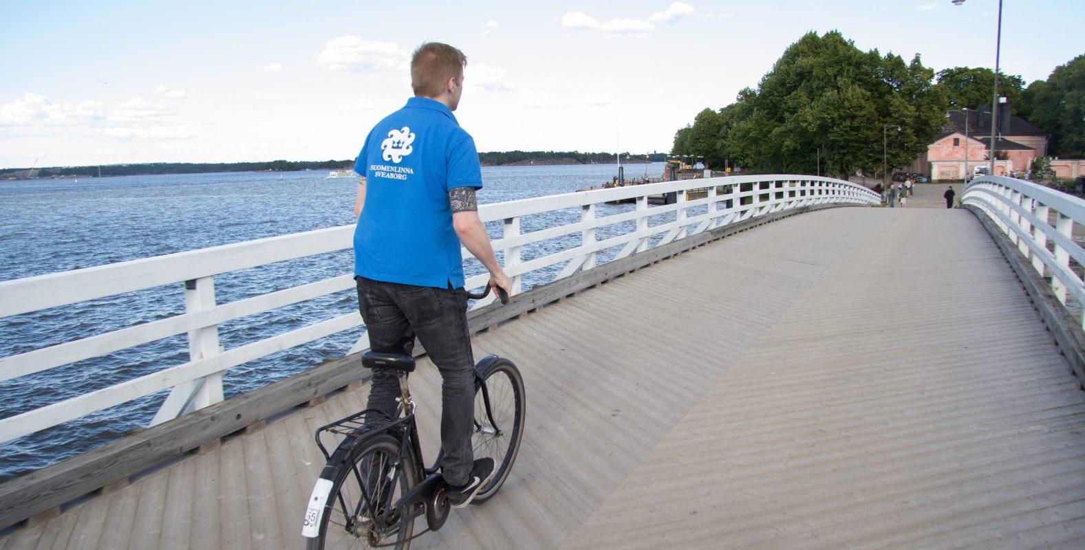 Kesävalvoja pyöräilee sillalla