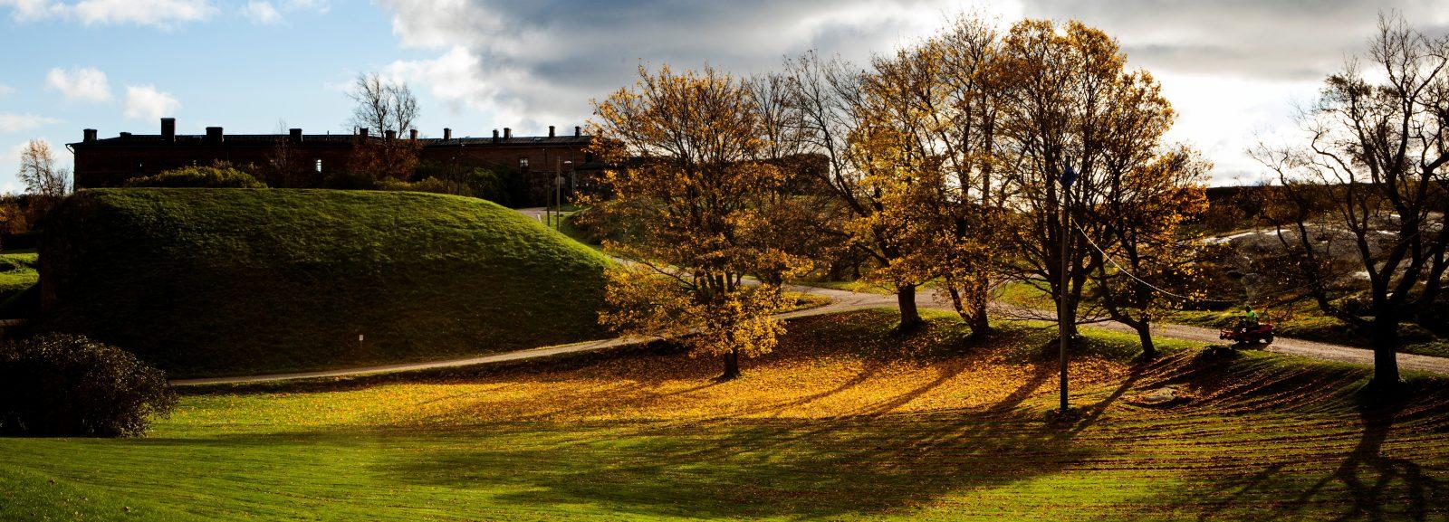 Syksyinen Suomenlinna, jossa näyy vihreä nurmikenttä ja värikkäät syksyiset puidenlehdet