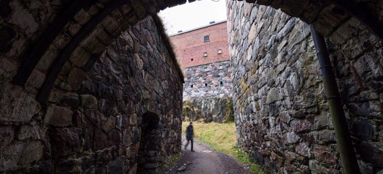 Kuvssa Suomenlinnan muuria, jonka edessä kävelee ihminen