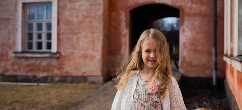 Kuvassa tyttö Miina asuinrakennuksen pihalla