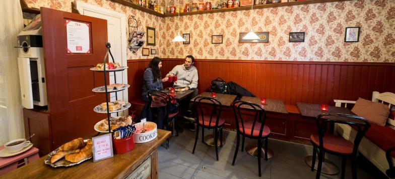 Cafe Vanille kuvattuna sisältä päin. Kuvassa kaksi kävijää, jotka kippistää kaakaomukeilla ja hymyilevät.