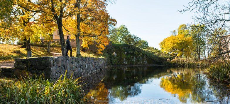 Kuvassa Piperin lampi syksyisessä maisemassa. Vasemmalla lammen reunalla seisoo mies.