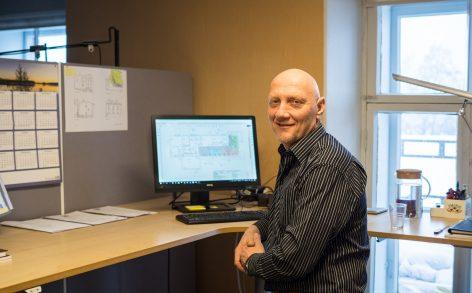 Rakennuttaja Pekka Vuorela istuu työpöydän ääressä. Työpöydällä on tietokone, jossa näkyy pohjapiirustus.