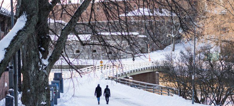 Talvinen linnoitus, jossa kaksi matkailijaa kävelemässä kohti Susisaaren siltaa. Taustalla muuria.