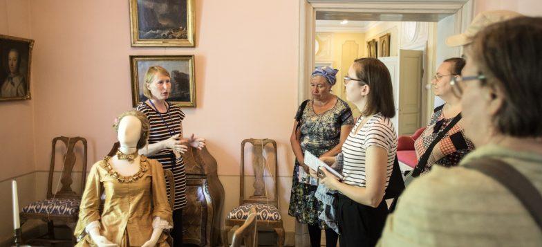 Kuvassa opas ja kävijöitä Ehrensvär-museossa. Kuvassa lisäksi museoesineitä, kuten tauluja ja mallinukke