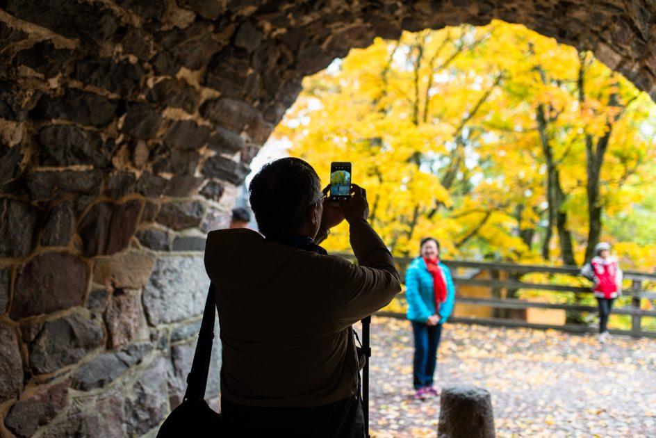 Aasialainen matkailija ottaa valokuvaa seuralaisestaan syksyisessä Suomenlinnassa.