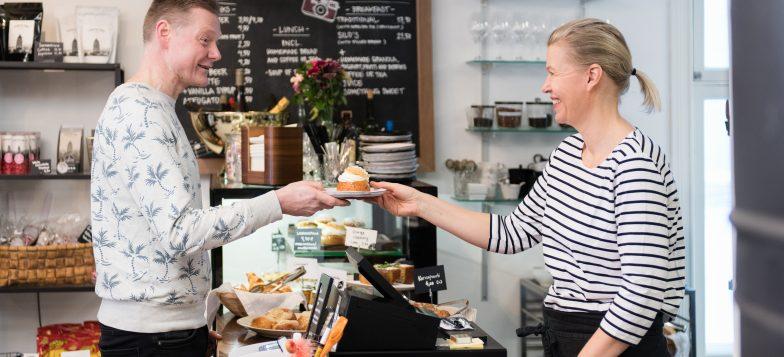 Kahvilayrittäjä ojentamassa laskiaispullaa asiakkaalle