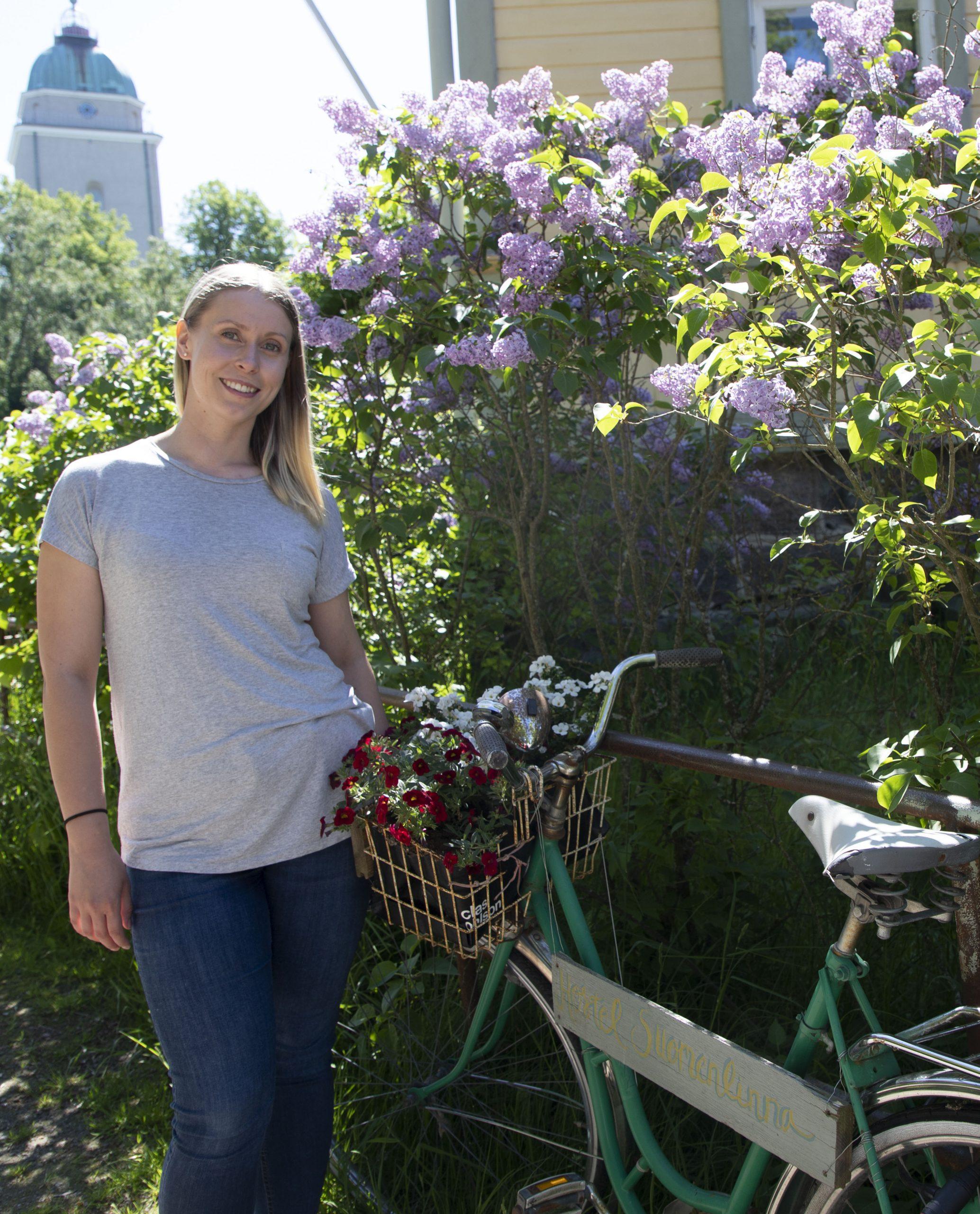 Elina Kokko seisomassa Suomenlinnan hostellin pyörän vieressä syreenien keskellä.