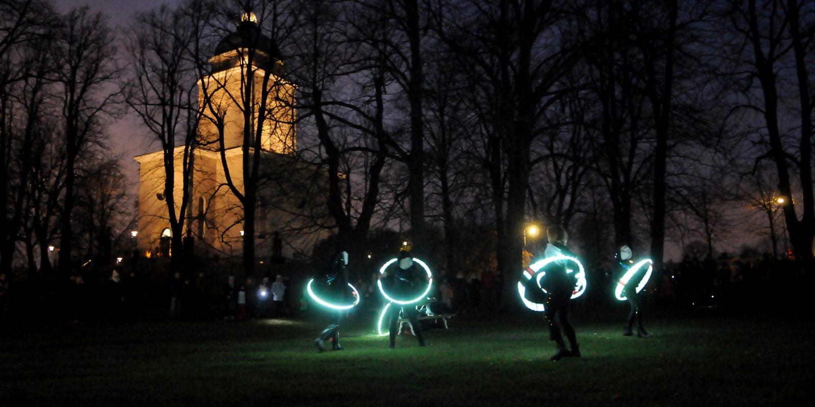 Valokuva Kirkkopuistosta, missä valosirkus Spektri pyörittää valaistuaja hulavanteita ja kirkko näkyy taustalla.