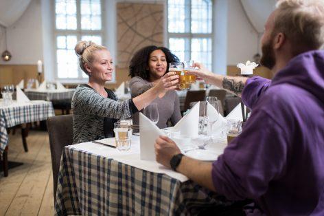 Ravintolavieraita istumassa ravintolan sisällä ja kippistämässä.