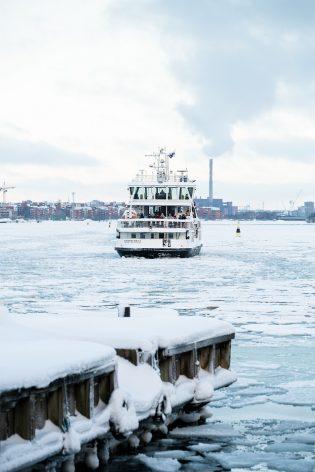 Suomenlinnan lautta ajamassa kohti laituria talvisessa maisemassa.