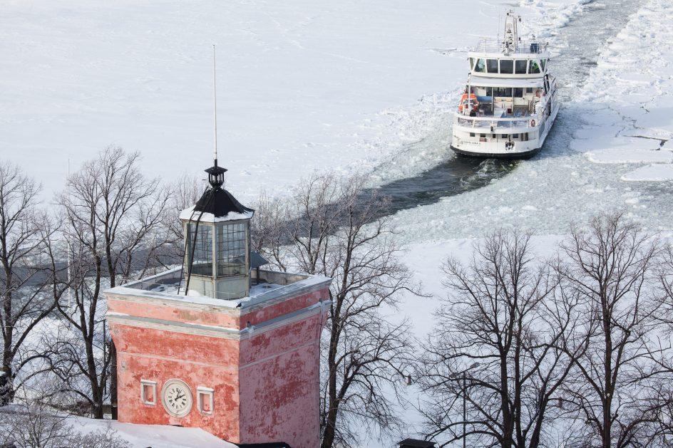 Ilmakuva, jossa näkyy rantakasarmin kellotorni ja suomenlinnan lautta talvisessa maisemassa