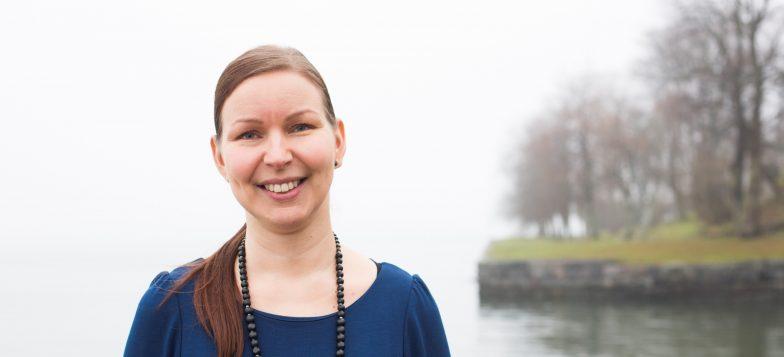 Matkailuasiantuntija Milla Öystilä seisoo sumuisessa Suomenlinnassa meren edustalla. Taustalla näkyy vehreää puistoa