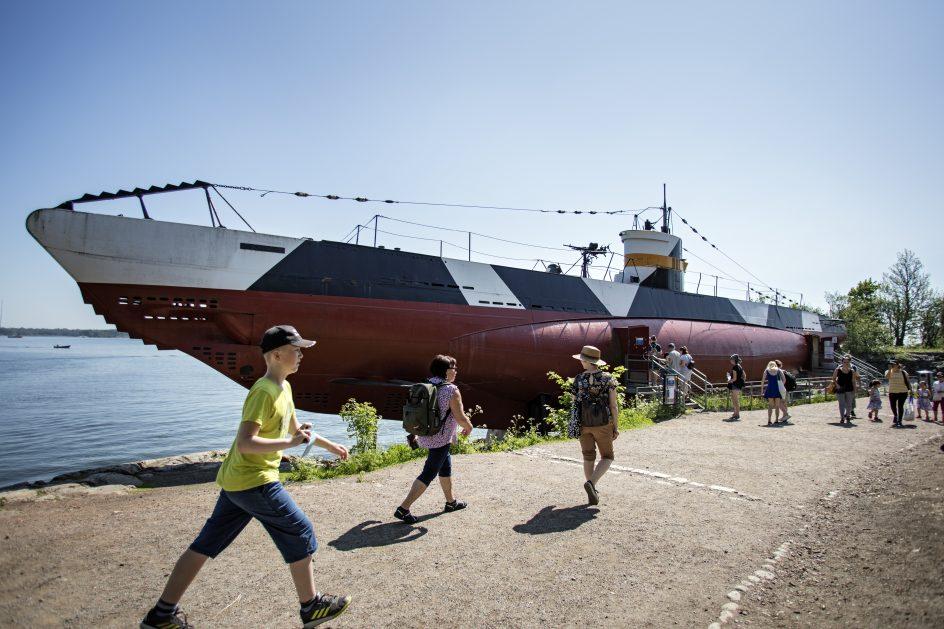Ihmiisä kävellessä kesällä sukelusvene Vesikon edessä.