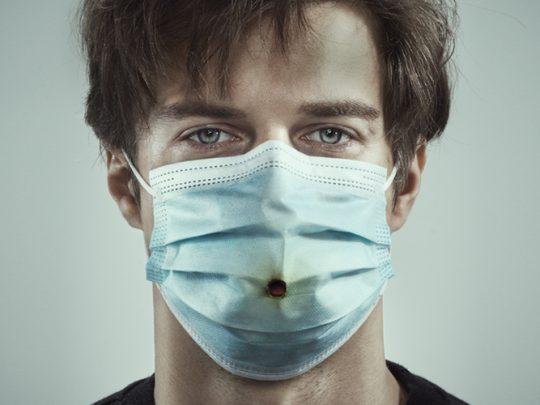 Miehen kasvot jolla kasvomaski johon poltettu tupakalla reikä