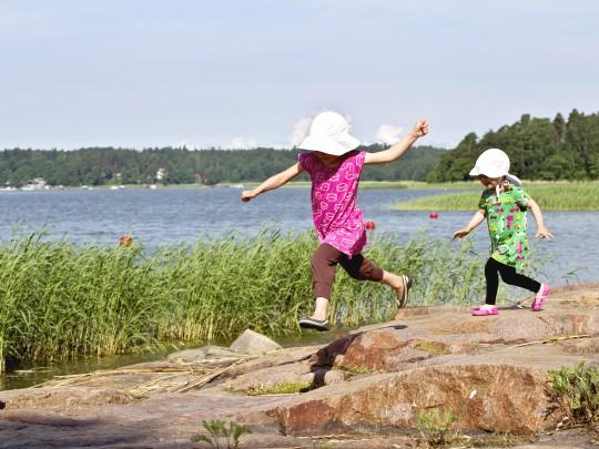 Kaksi lasta juoksemassa kallioilla merenrannalla. Kuva sivustolla Ilman syöpää.