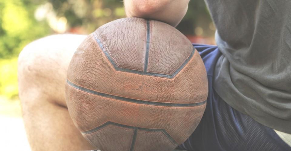 Kuvassa koripallo, johon istuva mies nojaa. Kuva sivustolla Ilman syöpää.