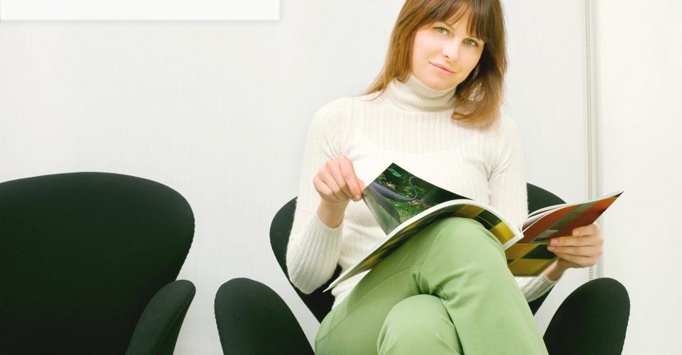 Nainen lääkärin odotussalissa lukemassa lehteä. Kuva sivustolla Ilman syöpää.