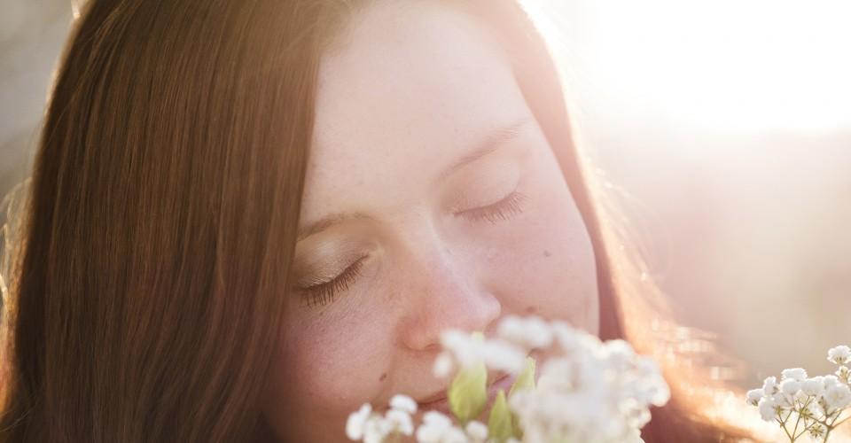 Nainen nuuskii silmät kiinni kukkia. Kuva sivustolla Ilman syöpää.