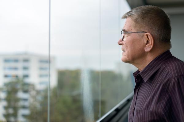 Mies katsoo ulos lasitetulla parvekkeella