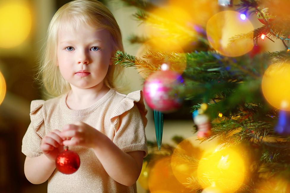 Lapsi pitelee joulukoristetta kädessä.