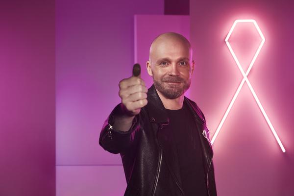 Juha Tapio näyttää peukkuaan takanaan Roosa nauhan muotoinen neonvalo.