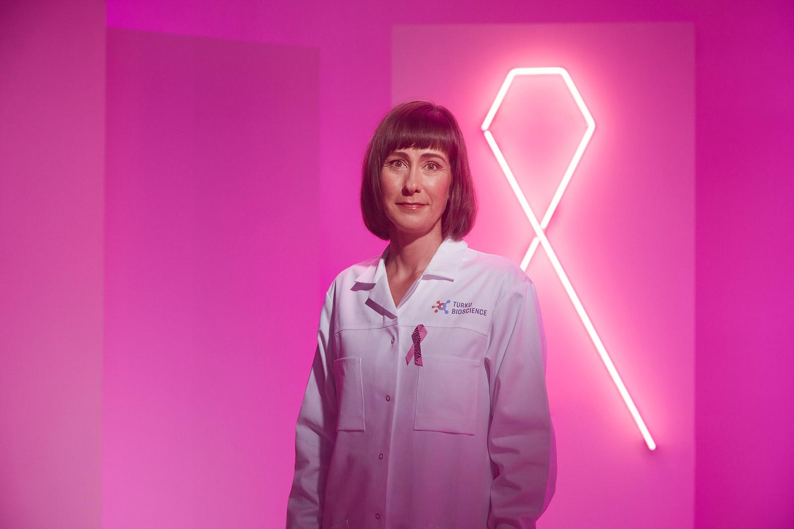 Kuvassa tutkija Johanna Ivaska Roosa nauha -valon edessä.