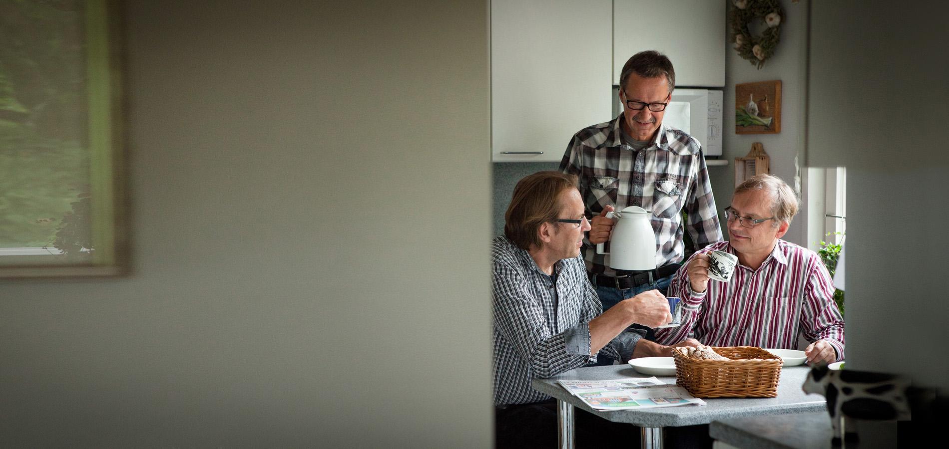 Kolme miestä keskustelee keskenään kahvia juodessaan.